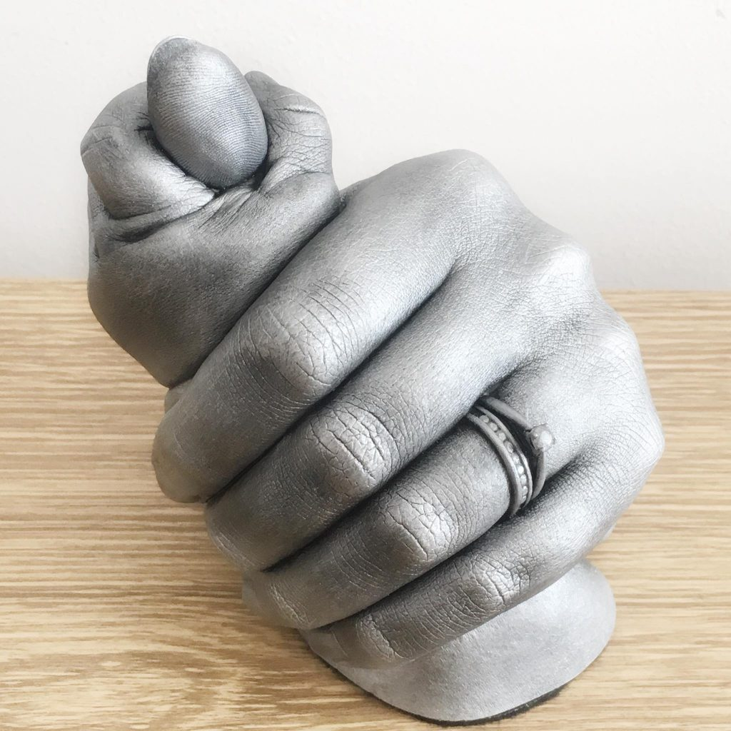 parent holding their babies hand in a 3d life cast finished in antique silver