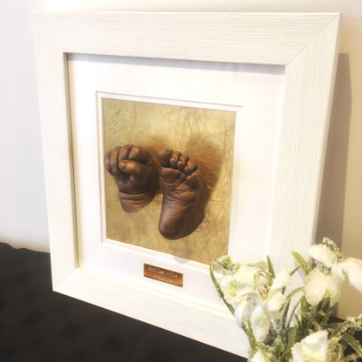 two baby casts hand and foot moulds framed in a white frame