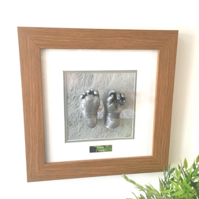 two baby casts hand and foot moulds framed in an oak frame