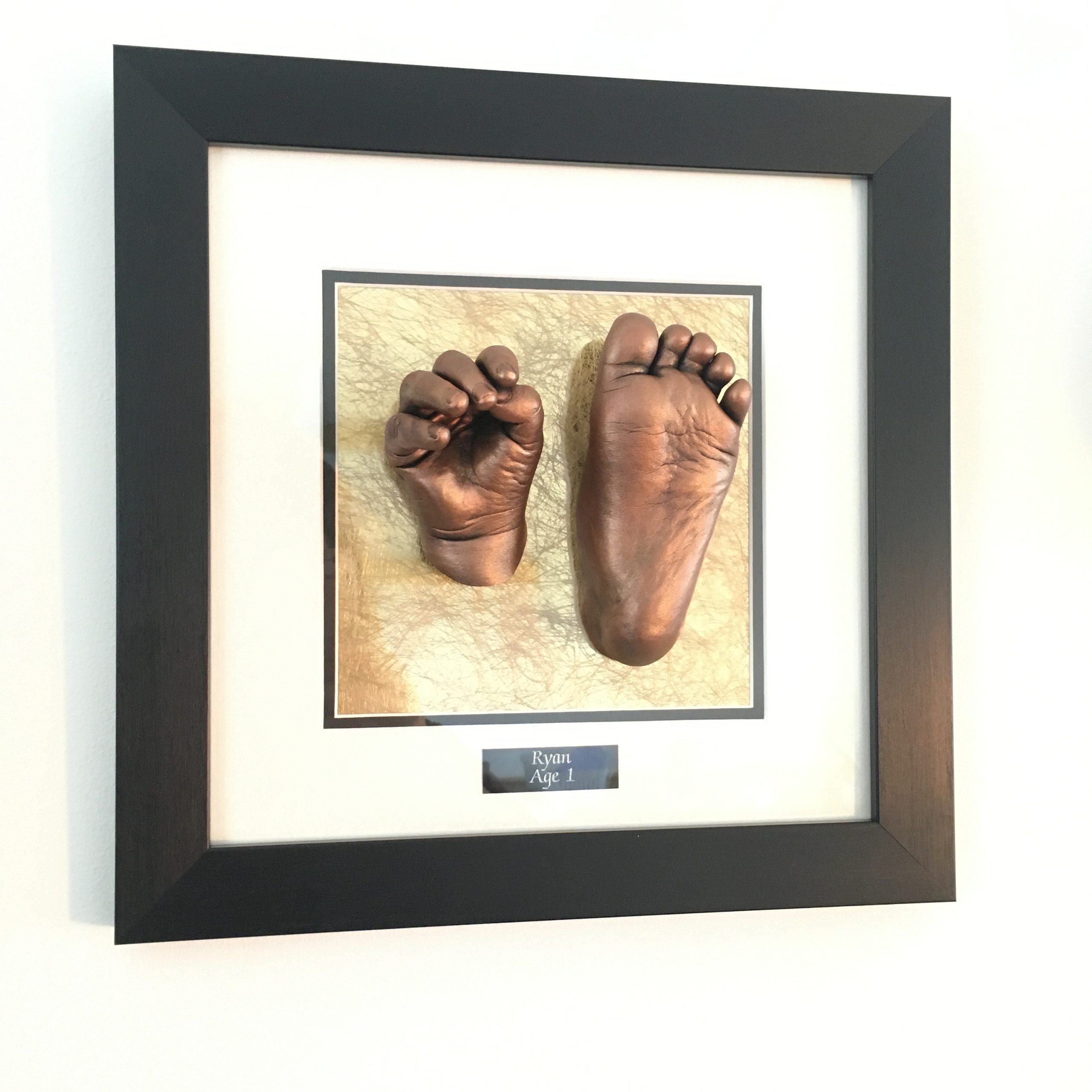 two baby casts hand and foot moulds framed in a black frame