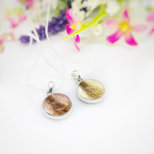 round resin silver charm filled with a lock of hair, cremation ashes or pet fur.
